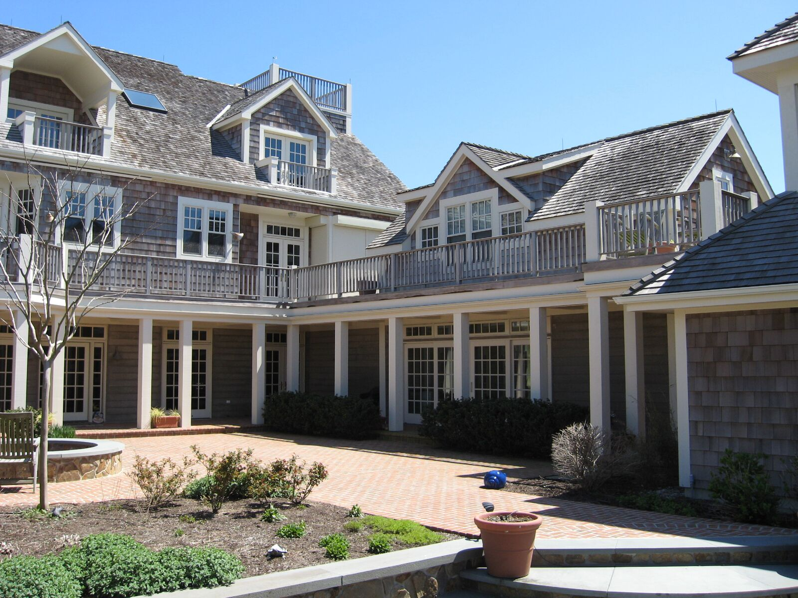 Shingle style ocean front beach house with cedar shingle siding and roofing, Pella windows and doors, Ipe decking and rails; lakeside patio with fire pit, fishpond, and garden walk.