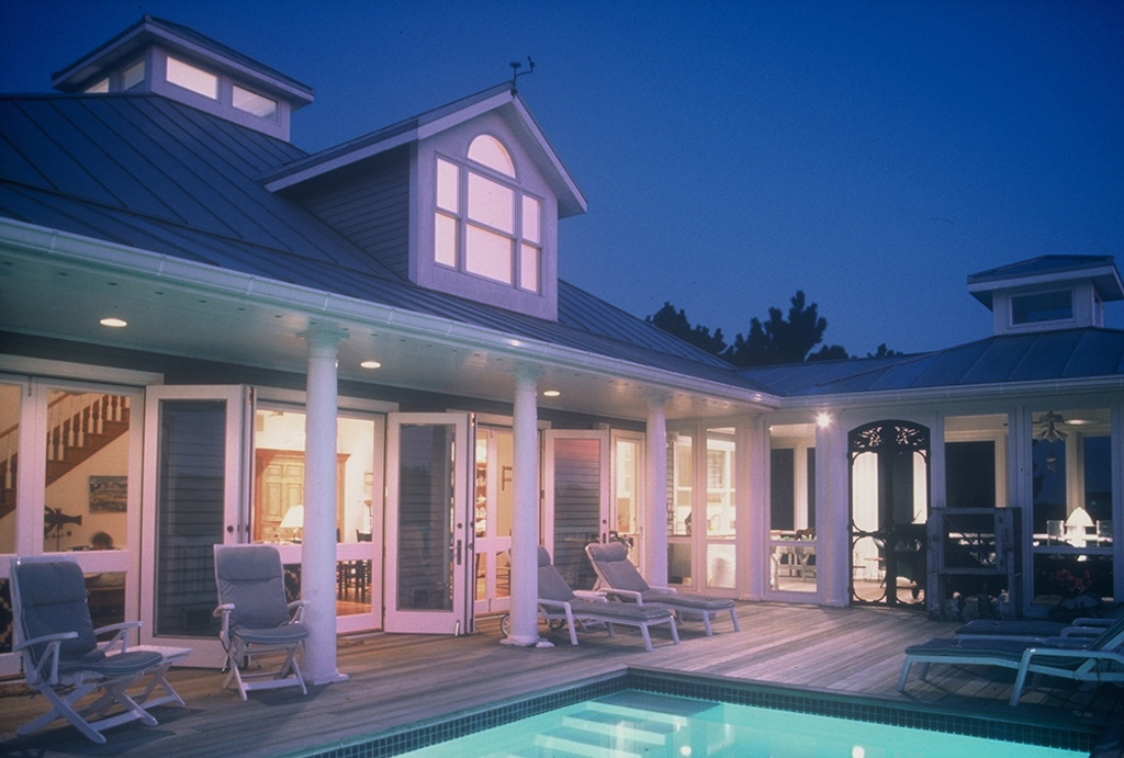 Custom beach home with in-ground pool and numerous pairs of French doors create an indoor outdoor living area.