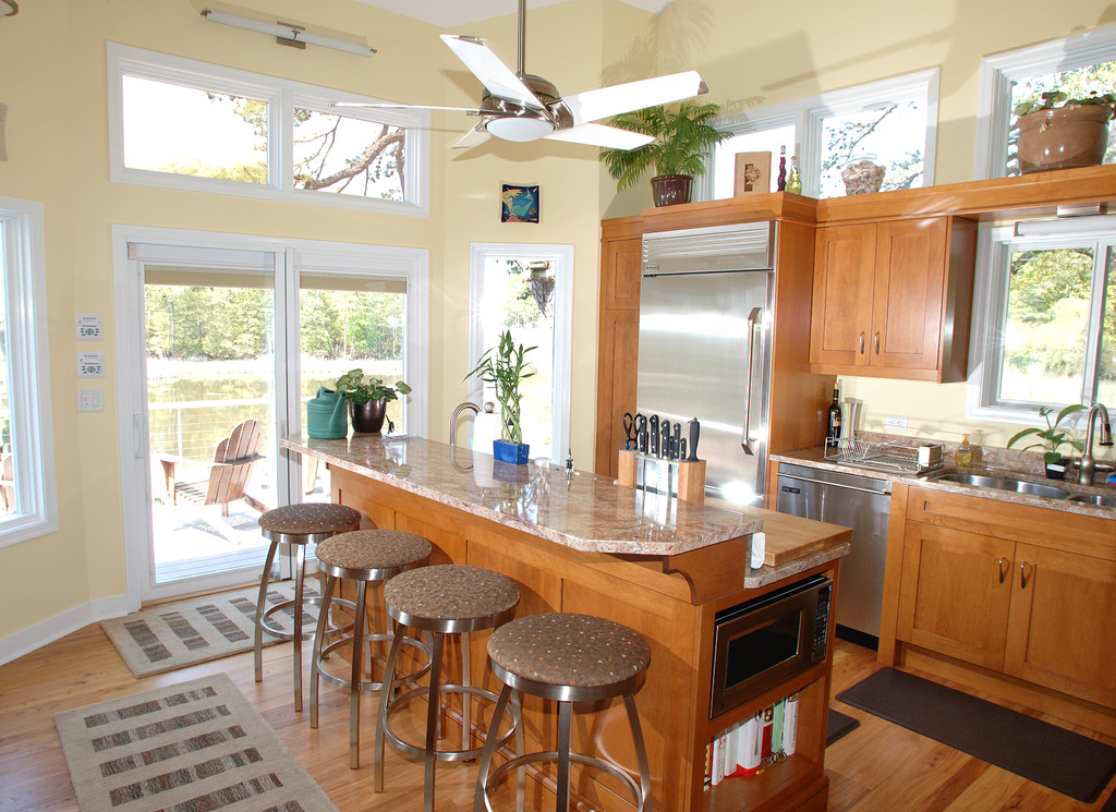 Canal front kitchen with stainless steel appliances, granite counters and shaker style cabinets.