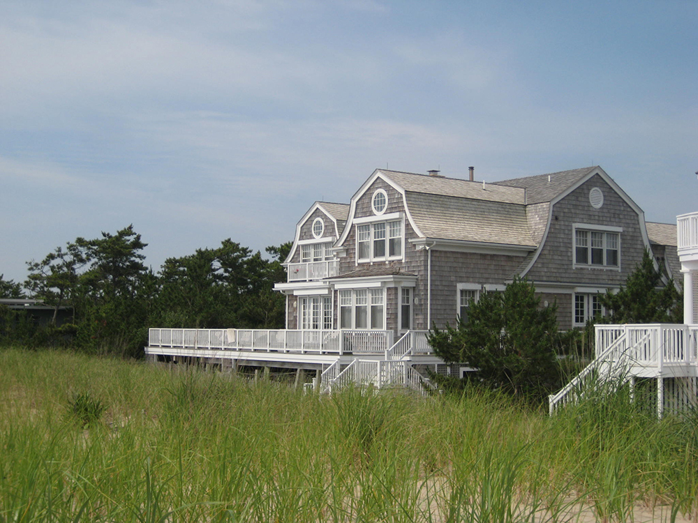 Traditional, shingle style beach house. Dutch-Gambrel roof with Pella windows and cedar shingle siding and roofing.